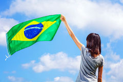 Woman holding a brazil flag. With clear blue sky stock images