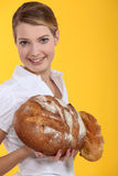 Woman holding bread. Woman holding round loaves of bread Royalty Free Stock Image
