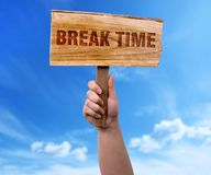 Break time wooden sign. A woman holding break time wooden sign on blue sky background royalty free stock photos