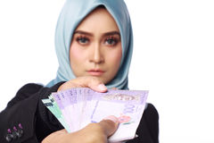 Woman holding a bribery money. A photo of woman holding a bribery money isolated in white background Royalty Free Stock Images
