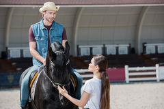 Woman holding bridle while handsome man in cowboy hat sitting on horseback. Young women holding bridle while handsome men in cowboy hat sitting on horseback Royalty Free Stock Images