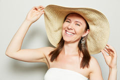 Woman holding brim of straw hat. Smiling happy woman holding brim of straw hat with her hands stock photography
