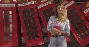 The woman holding British flag and book, education abroad, learning language. The woman holding British flag and book, education abroad, learning language stock video footage