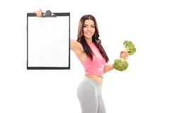 Woman holding a broccoli dumbbell and clipboard Stock Photography