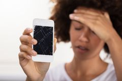 Woman Holding Broken Mobile Phone. Close-up Of A Young Woman Holding Broken Mobile Phone royalty free stock images