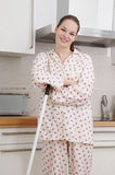 Woman holding a broom. Woman in pajamas holding a broom kitchen in a modern kitchen stock photography