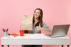 Woman holding brown clear empty blank craft paper bag showing thumb up work at office with laptop isolated on pink. Background. Food products delivery courier royalty free stock photography