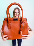 Woman holding brown leather handbag. Stock Photo
