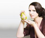 Woman Holding Bruised Fruit. Beautiful woman wrinkling her nose in disgust at an unappetising pear with a bandaid cross in a Bruised fruit or unappealing healthy Royalty Free Stock Photography