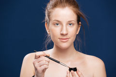 Woman holding brush and cream. Beauty portrait of a young woman holding brush and cream over blue background Royalty Free Stock Images