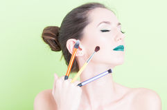 Woman holding brushes posing with professional trendy make-up Stock Photography