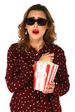 Woman holding bucket with popcorn and watching blockbuster movie in stereo glasses. Emotional young woman holding bucket with popcorn and watching blockbuster Stock Photography