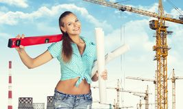 Woman holding builders level on shoulder and paper Stock Image