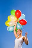 Woman holding bunch of balloons Stock Photo
