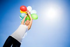 Woman holding bunch of balloons Royalty Free Stock Photography