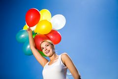 Woman holding bunch of balloons Royalty Free Stock Images