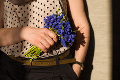 Woman holding a a bunch of beautiful spring blue flowers. Sunshine in spring Stock Photography