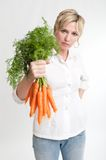 Woman holding a bunch of carrots Stock Images