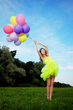 Woman holding bunch of colorful air balloons Royalty Free Stock Image