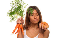 Woman holding bunch of fresh carrots and roll Stock Photos