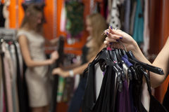 Woman holding bunch of garments in shop, closeup. Close up of hands of young beautiful women holding bunch of hangers with different dresses. Lady doing shopping Stock Image
