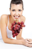 Woman holding a bunch of grapes by her teeth Royalty Free Stock Image