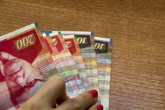 Woman holding a bunch of Israeli New Sheqel banknotes in her han Stock Photo