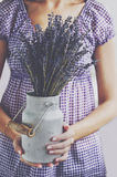 Woman holding bunch of lavender in old milk churn Stock Photography