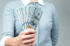 Woman holding bunch of money banknotes. Bundle of bills of one hundred dollars in female hands Royalty Free Stock Photography