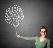 Woman holding a bunch of smiling balloons Royalty Free Stock Images