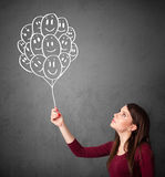 Woman holding a bunch of smiling balloons Stock Photo