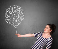 Woman holding a bunch of smiling balloons Royalty Free Stock Image