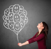 Woman holding a bunch of smiling balloons Royalty Free Stock Photo