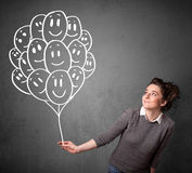 Woman holding a bunch of smiling balloons Stock Image