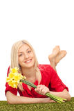 Woman holding a bunch of tulips and lying on grass Royalty Free Stock Photo