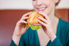 Woman Holding Burger In Coffeeshop Royalty Free Stock Image