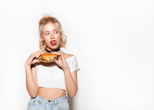 Woman holding burger and licking lips Stock Images