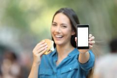 Woman holding a burger showing a phone screen Royalty Free Stock Images