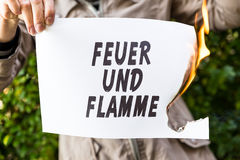 Woman is holding a burning paper with german text Stock Photography