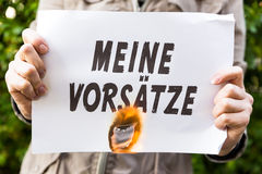 Woman is holding a burning paper with german text Royalty Free Stock Photography