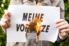 Woman is holding a burning paper with german text Royalty Free Stock Photo