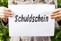 Woman is holding a burning paper with german word Stock Images