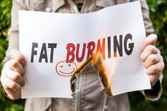 Woman is holding a burning paper with text Stock Photos