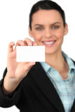 Woman holding business card. Woman all smiles holding business card Royalty Free Stock Photos