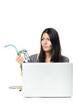 Woman holding Cables in her  hand while Using Laptop Royalty Free Stock Images