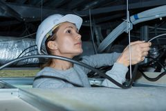 Woman holding cables overhead in roofspace. Female Stock Images