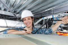 Woman holding cables overhead in roofspace. Female Royalty Free Stock Photo