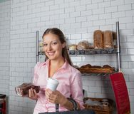 Woman Holding Cake And Coffee Cup At Supermarket Stock Image