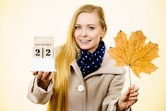Woman holding calendar with first autumn day. 22 september and big leaf. Studio shot on yellow background Stock Photos