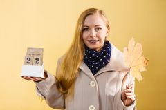 Woman holding calendar with first autumn day. 22 september and big leaf. Studio shot on yellow background Royalty Free Stock Photos